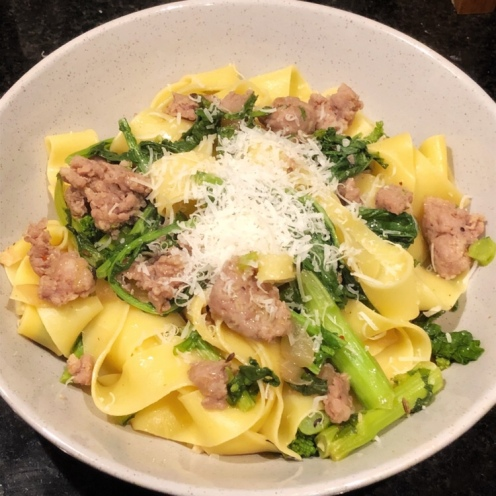 Pappardelle with Italian Sausage and Cima di Rapa. The meat and vegetable are tossed through starchy pasta cooking water to coat the pasta in a light sauce.
